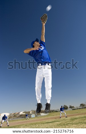 Baseball player, in blue uniform, jumping up to catch ball in protective glove during competitive game (surface level, tilt) Stock photo ©