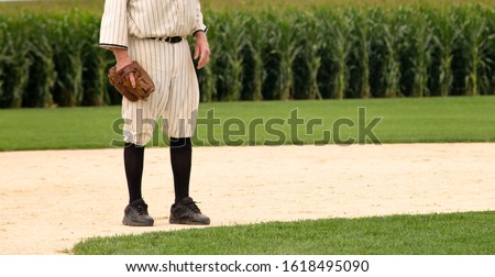 Baseball player in old baseball uniform and baseball glove, on the playing field.  Corn in the background.