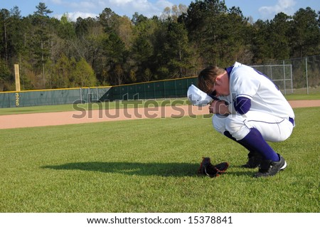 Baseball player pauses before game to pray for safety and sportsmanship.  His hat is off and glove is on ground in front.