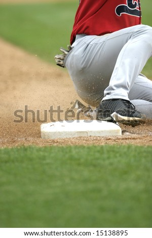 baseball player slides safely into third base