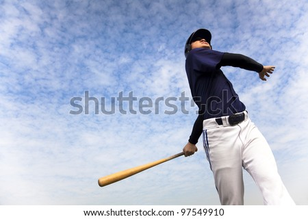baseball player taking a swing with cloud background