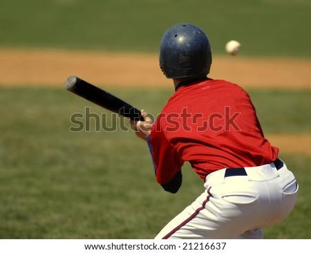 Baseball player wearing uniform bunting a baseball while at bat