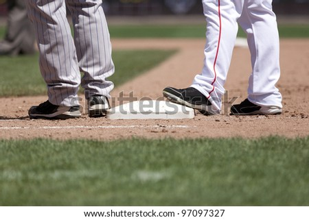 baseball players at 1st base on a sunny day