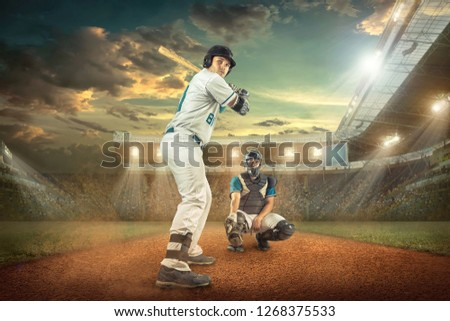 Baseball players in dynamic action action under sunset sky on the stadium. #1268375533