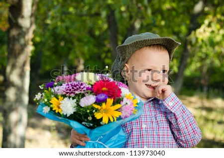 Bashful small boy smiling sheepishly with a bouquet of flowers for his sweetheart or Mum on Valentines or Mothers day