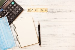 Basic income written on wood blocks with medical mask, calculator and notepad on white background. Back to basics fundamental principles concept