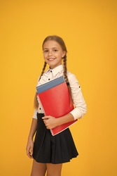 Basic level. Happy schoolgirl hold textbooks yellow background. Little schoolgirl back to school. Small schoolgirl wear uniform. Cute schoolgirl. School education. Courses for gifted children.
