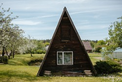 Basic triangular holiday cabin with blossoming garden in the back. Brown building with white window and white old-school curtains. Cabins and barns are wonderful start for a rental business.