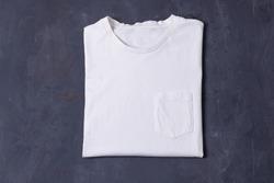 Basic white Tshirt on grey concrete background. Mock up for branding t-shirt with pocket.