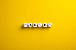 Basics word written on blocks on yellow background with flat lay view. Back to basics or simplifying business concept.