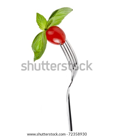 basil herb and tomato cherry on a fork isolated on white