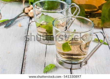 Basil herbal tea in a transparent cup and teapot, spoon with cane sugar, a bunch of fresh basil. On a white wooden table. Copy space