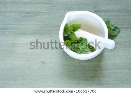 basil in mortar, wooden background, top view