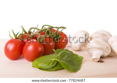 Basil leaves, red tomatoes and mushrooms on a wooden cutting board