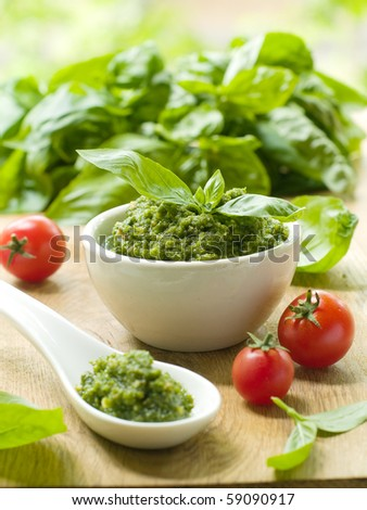 Basil pesto in a small bowl, with fresh basil leaves.