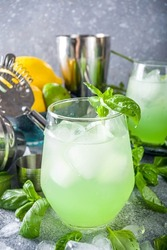 Basil smash gin alcoholic cocktail. Long alcohol drink recipe with fresh basil leaves and limes, grey stone background copy space