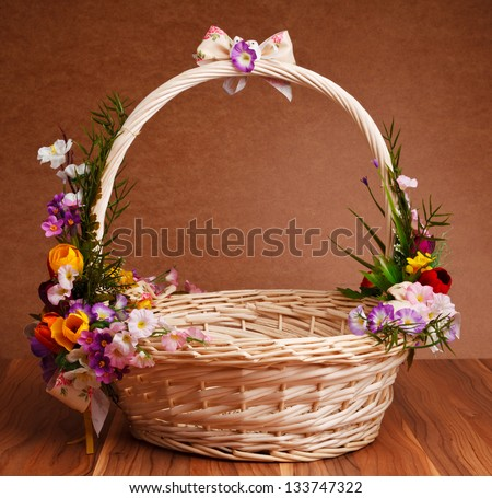 Basket Decorated With Flowers On Wooden Table Stock Photo