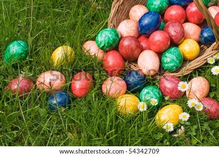 Basket full of Easter eggs in Grass - stock photo