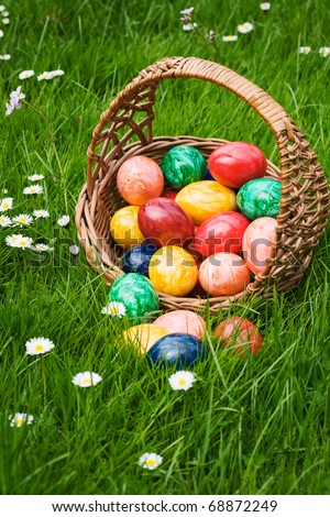 Basket full of Easter eggs in grass - stock photo