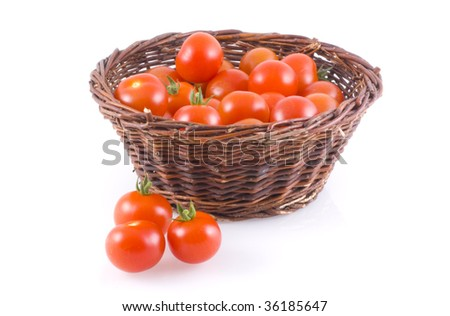 Basket full of tomatoes, with a few next to it, isolated on white.