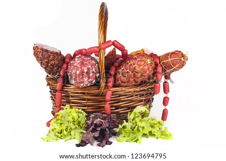 Basket full with salami and green salad aside