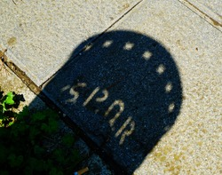 Basket in a park engraved with SPQR projects the shadow on the asphalt in the sun
