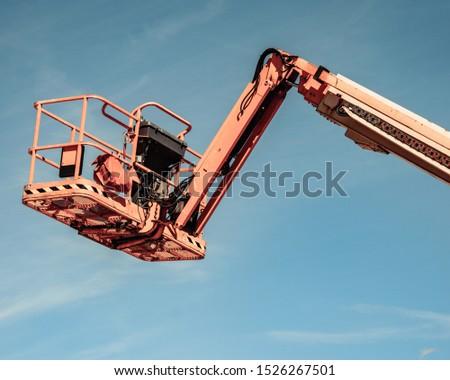 Basket lift, orange lifting platform on construction site. Industrial machine, work on height equipment concept.