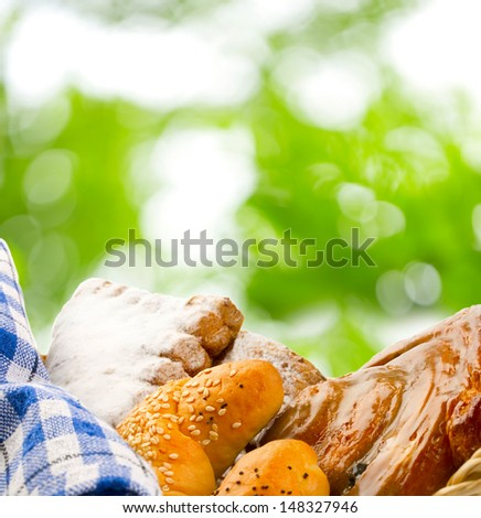 Basket of buns on green leaves background