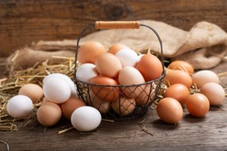 basket of colorful fresh eggs on wooden background