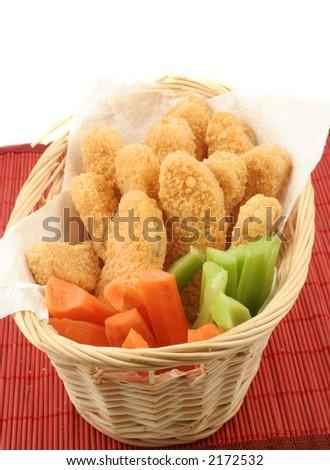 basket of crispy chicken fingers with platter of vegetables and dip