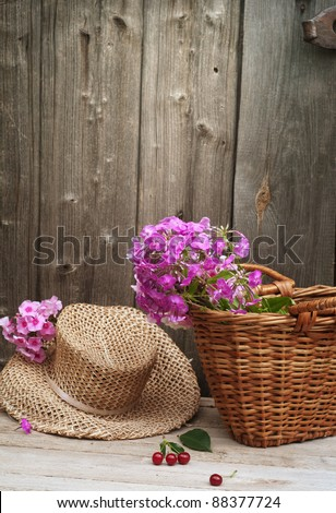 basket of flowers and a straw hat against the background of the old wooden walls