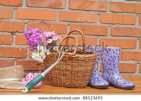 basket of flowers and gardening tools against a brick wall