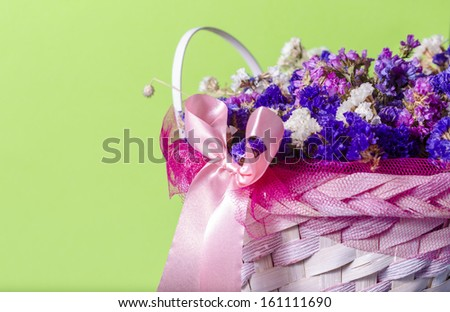 basket of flowers isolated on green background
