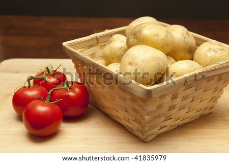 Basket of fresh raw potatoes next to red ripe tomatoes on the vine
