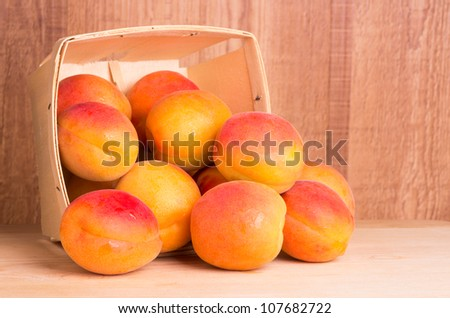 Basket of fresh ripe apricots on wooden table