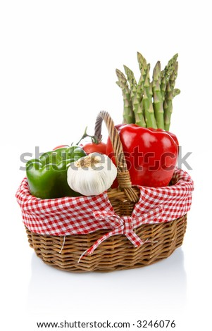 Basket of fresh vegetables reflected on white background