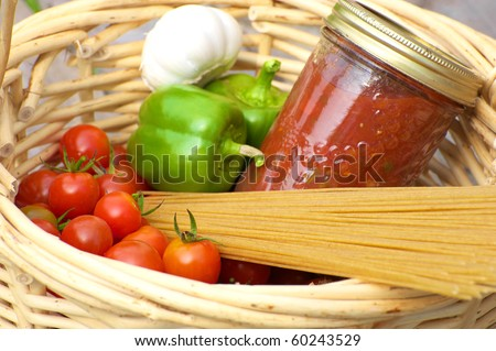 Basket of freshly picked organic vegetables, homemade pasta sauce and raw whole wheat pasta.