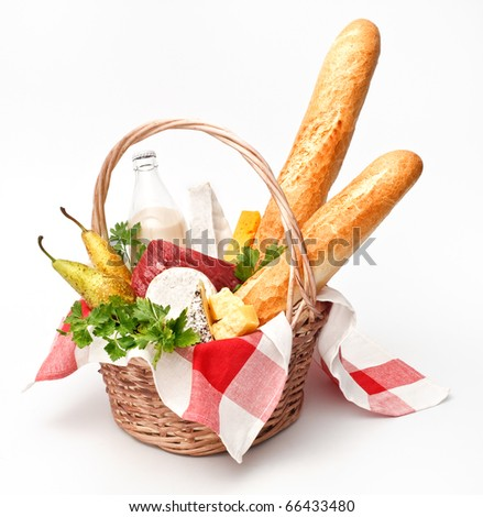 Basket of goods with cheese, bread and meat on white background