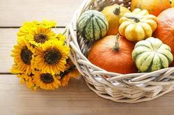 Basket of pumpkins on wooden table