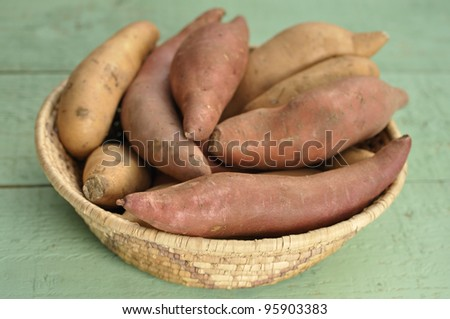 Basket of red yams and sweet potatoes on green table