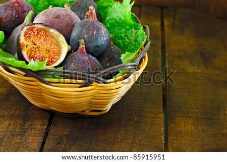 Basket of ripe figs on rustic wooden table