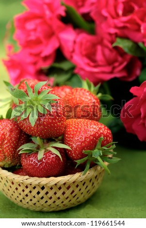 Basket of ripe strawberries and a bunch of red roses in a vase