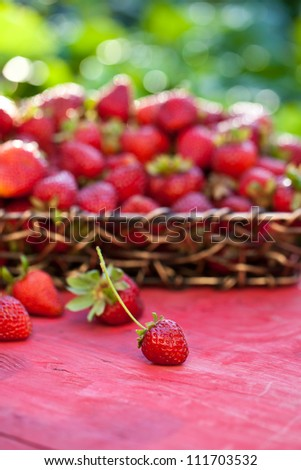 Basket of strawberries on red wooden surface with green background