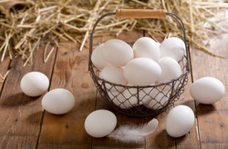 basket of white eggs on wooden table