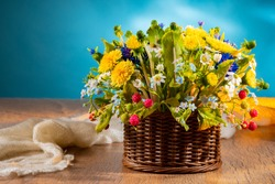 Basket of wild flowers on a blue background. Bright floral arrangement. Rustic still life with wild flowers and a soft shawl. The bouquet of bright plants is beautifully lit.