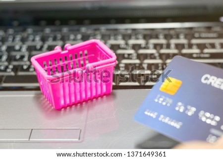 Basket shopping and hand holding mock up of credit card on laptop keyboard. Consumer can buy products directly anywhere anytime from seller using web browser. Online shopping and e-commerce concept.