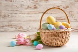 Basket with beautiful Easter eggs and flowers on table