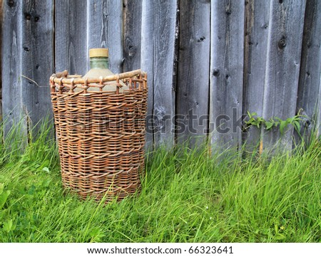 basket with bottle on green herb
