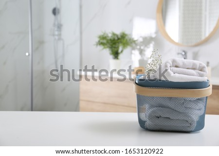 Basket with clean soft towels in bathroom. Space for text