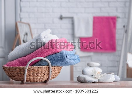 Basket with clean towels on table